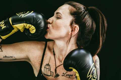 woman kissing black and yellow boxing glove