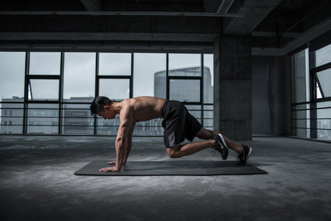 shirtless man working out on a black gym mat