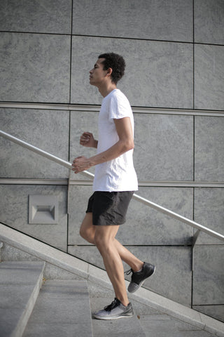 a man in a white t-shirt doing cardio on concrete steps
