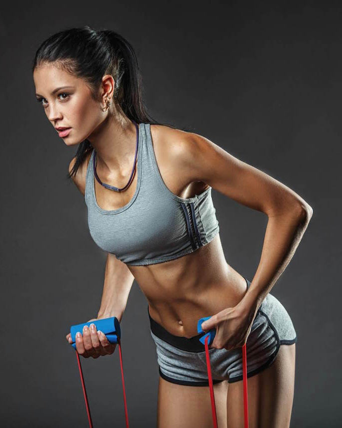 resistance-bands-exercises-toned-woman-gray-croptop-grey-sports-shorts