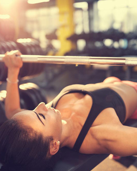 woman-black-crop-top-lying-down-doing-chest-press-with-barbell-in-gym