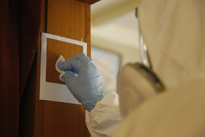 Person in white hazmat suit with blue gloves taking a swab sample in a building for an IANZ accredited meth test