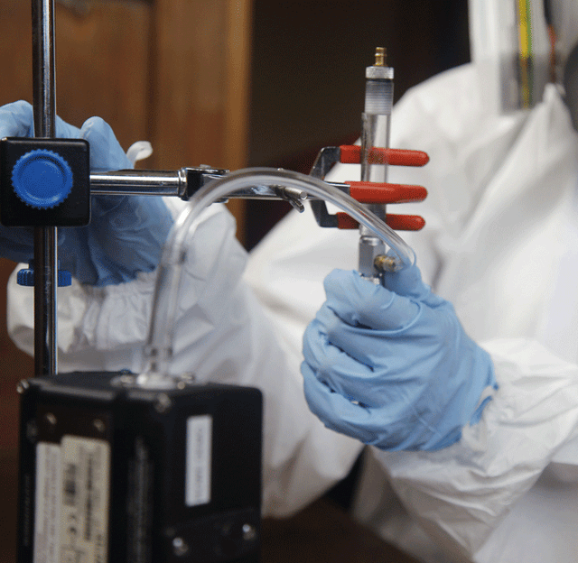 Person in white hazmat suit, blue gloves, and respirator holding sampling tube connected to a pump to collect indoor air quality samples