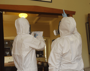 Person in white hazmat suit taking asbestos notes on a clipboard while another person in a white hazmat suit points at a building material during an asbestos survey