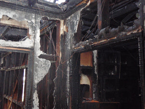 Badly fire-damaged walls and ceilings that only show the timber framing of a house after a fire
