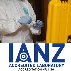 Person in white hazmat suit and blue gloves placing cotton swab into vial during a meth test with the IANZ logo