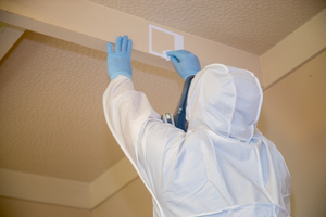 Person in white hazmat suit and blue gloves collecting a swab sample from a ceiling in a residential home during a meth test