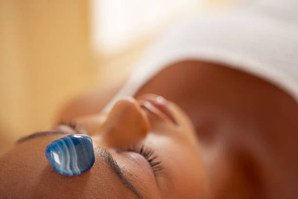 woman laying down receiving crystal healing treatment with blue agate on forehead