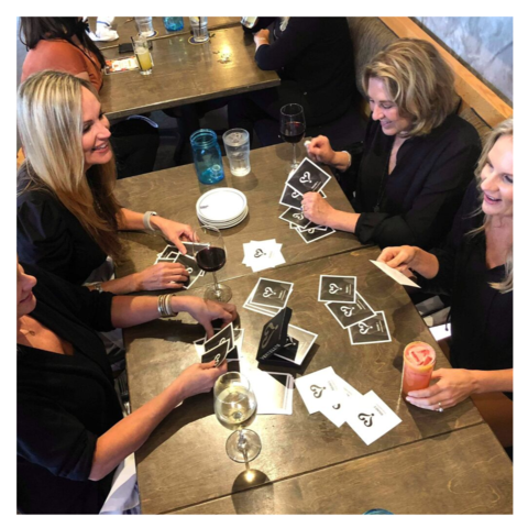Group of women laughing and playing Vertellis Holiday Edition at restaurant.