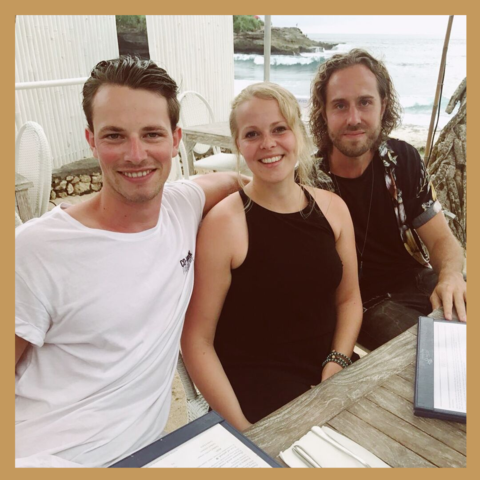 Lars, Liz, and Bart, the co-founders of Vertellis, smiling and working on a beach in Bali.