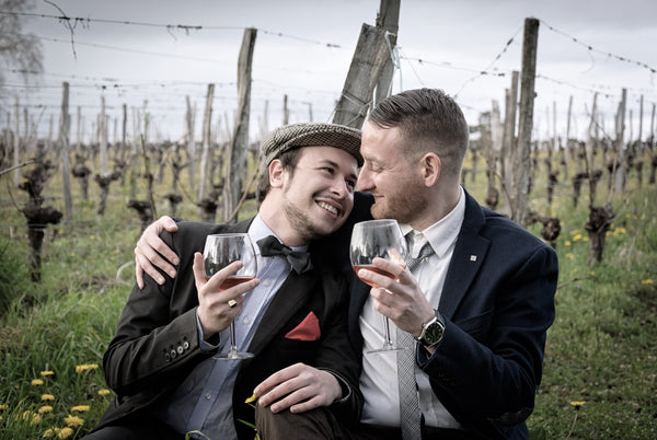 Male couple hugging while holding wine glasses