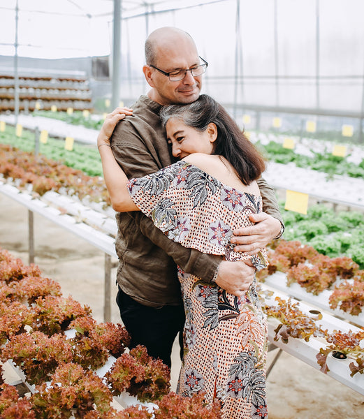 Retired couple embracing in plant nursery.