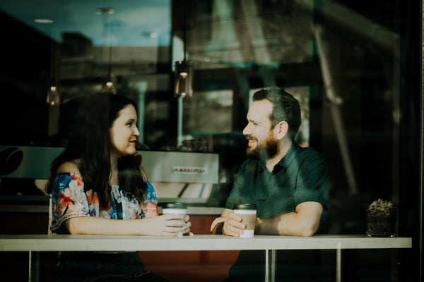 Couple sitting and having conversation at coffee shop.