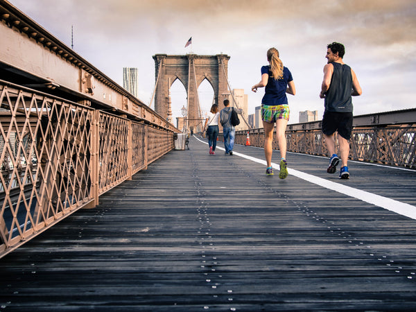Couple running together on Brooklyn bridge
