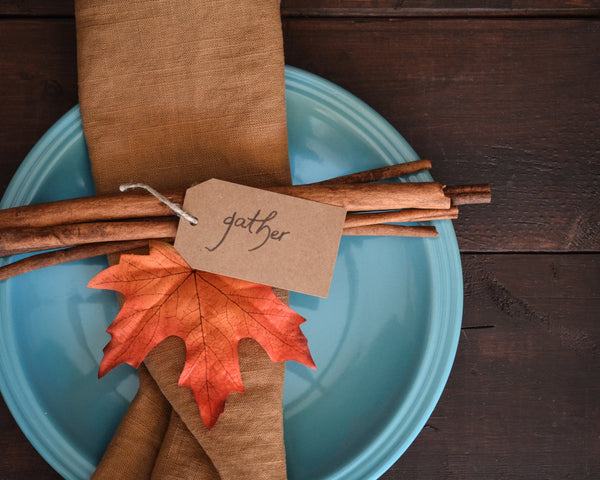 Napkin folded with leaf on top of blue plate with note that says gather.