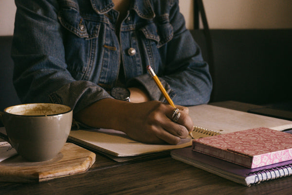 Woman writing in journal next to coffee cup.