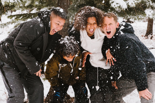 Group of men and women laughing and playing in snow.