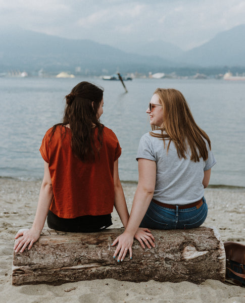 Two friends sitting on driftwood on beach talking