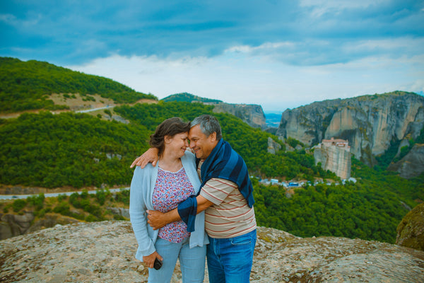 Older couple smiling and holding each other in front of beautiful green vista.
