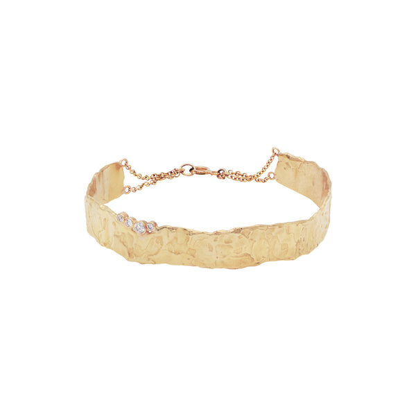 This bracelet is one of the showpieces from The Rode collection. The Rode bracelet is made in 14-karat gold with four diamonds 0.14 ct. The bracelet is hand sculptured with Fie Isolde's raw signature look. It lays nicely on the wrist and is closed with a lobster clasp. Wear it by itself like a classic statement piece or stack it with one of Fie Isolde's other bracelets like The Odette or The Luna.