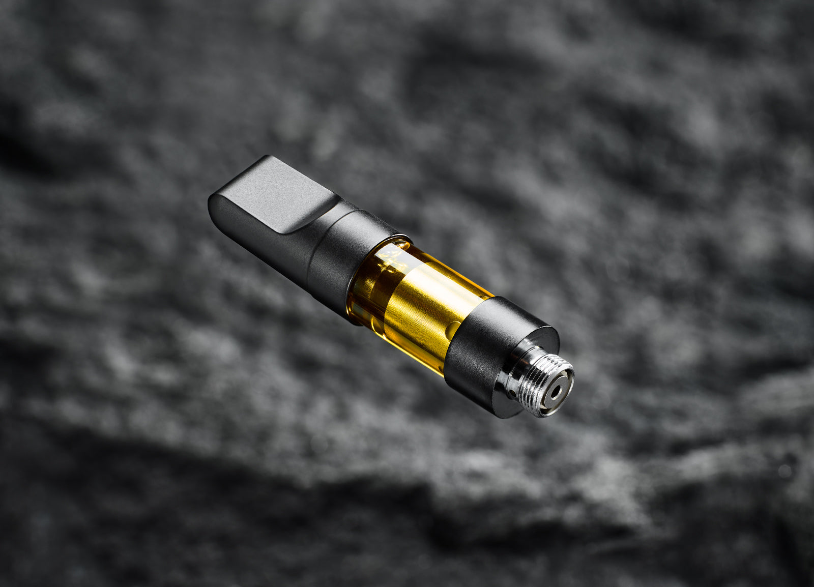 vape cartridge hovering over blurred black background