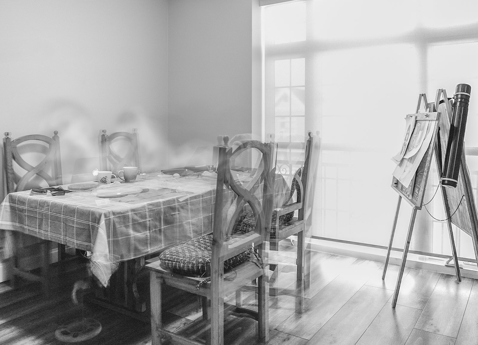 black and white photo of table set for four by window