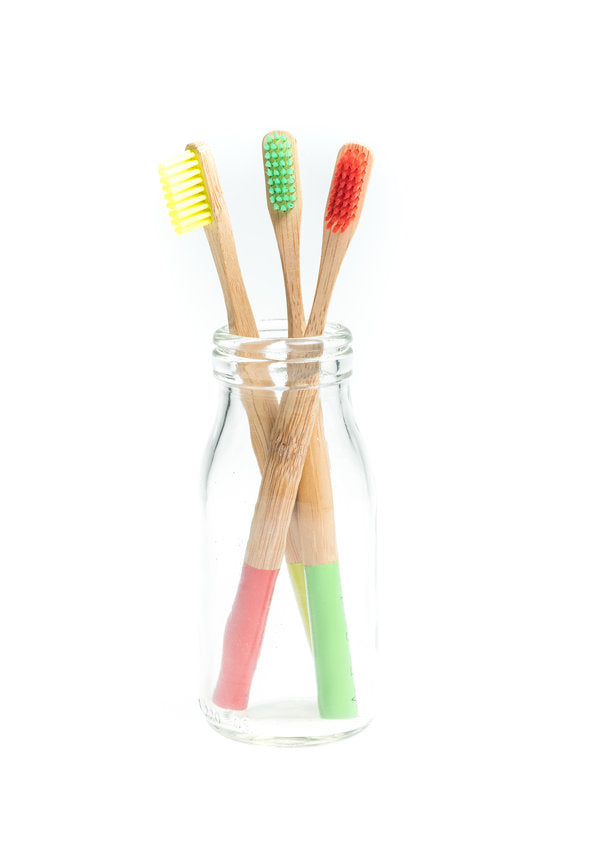 Yellow green and pink bamboo toothbrushes in a jar
