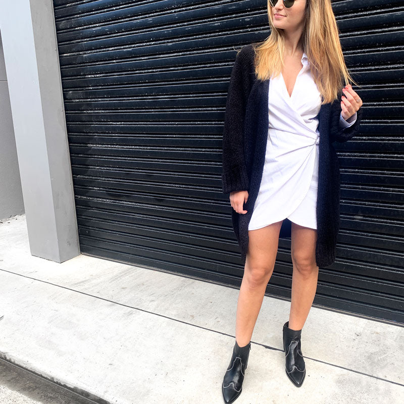 model in white dress, black cardigan and Black leather, western heeled Billi Bi ankle boots with silver stud detail