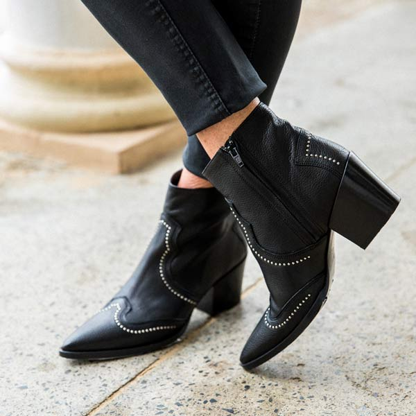 model in black jeans and Black leather, western heeled Billi Bi ankle boots with silver stud detail close up