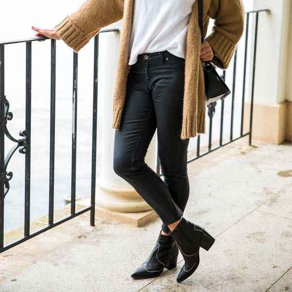 model in black jeans, camel cardigan and Black leather, western heeled Billi Bi ankle boots with silver stud detail
