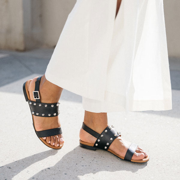 Black textured leather Billi Bi flat sandal with silver stud detail on model walking in white linen pants