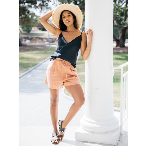 Black leather Billi Bi flat sandal with silver stud detail on model in shorts, cami, sunhat leaning against white column