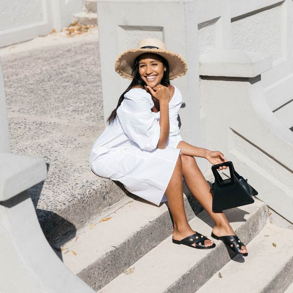 Model sitting on concrete steps wearing white dress, sunhat and Black textured leather Billi Bi flat crossover slide with gold stud detail