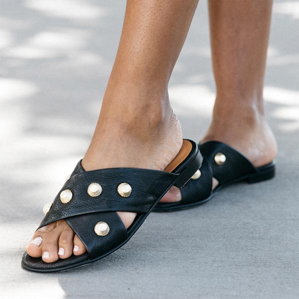 close up of Black textured leather Billi Bi flat crossover slide with gold stud detail on model's feet