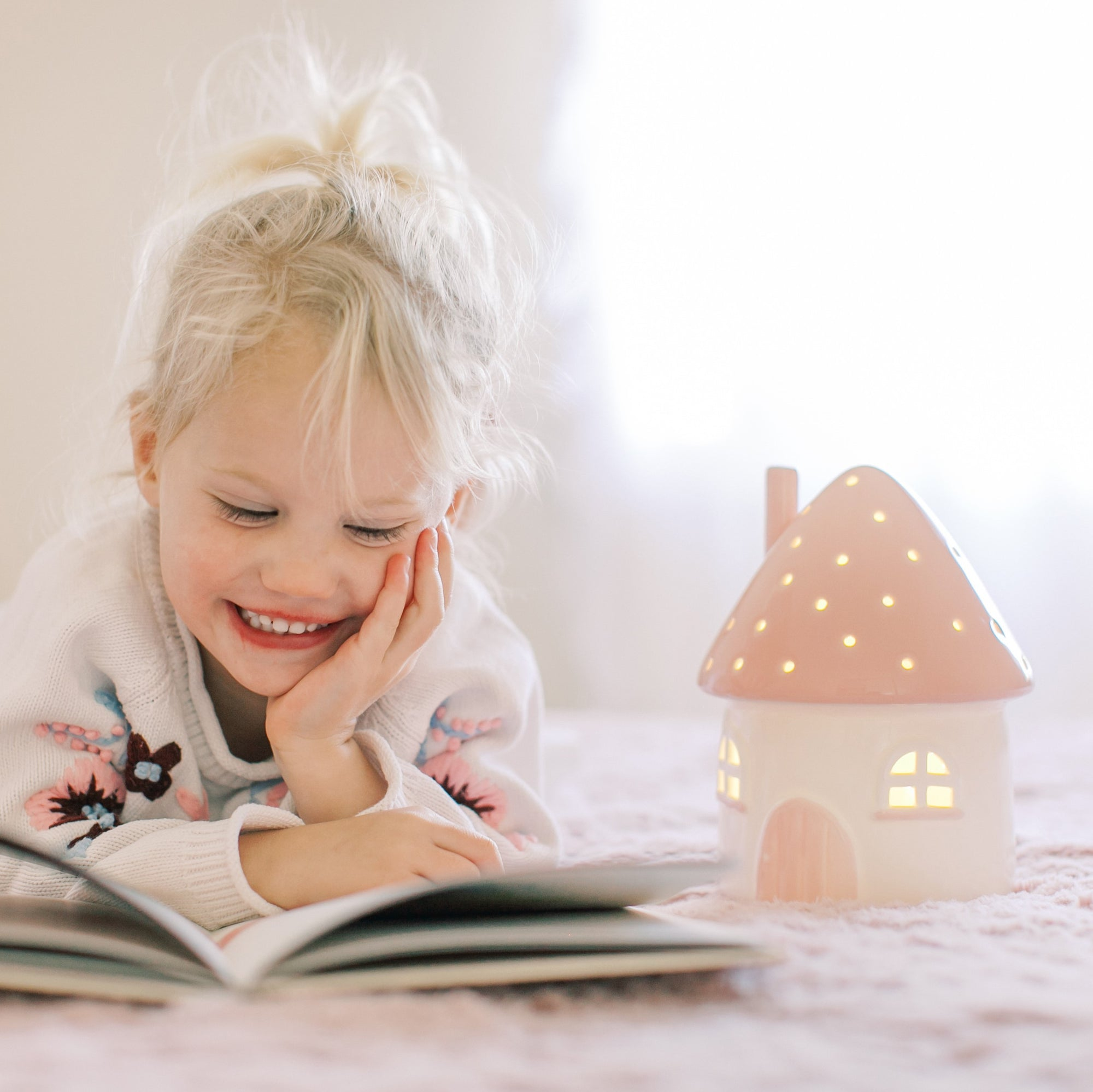 Girl reading book with night light