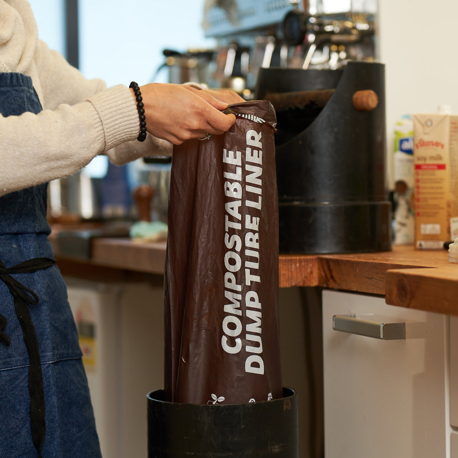 Compostable coffee dump tube liner for cafe's. Picture of liner being used.