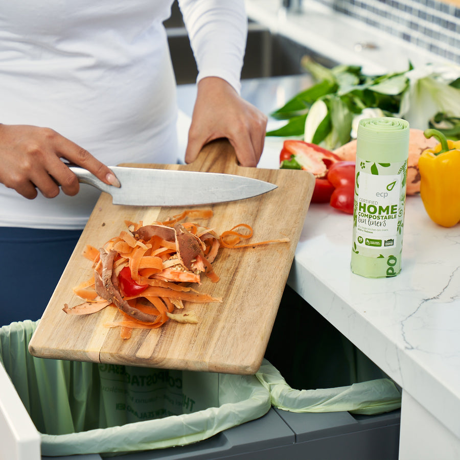Home Compostable 35L Kitchen Bin Liner. Perfect for lining your home or business pull out kitchen bin. Picture showing food scraps being scraped into the bin from a chopping board.