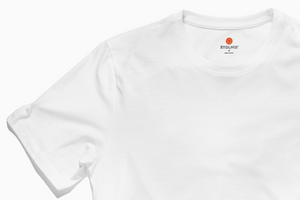 Zoom image of Stolmid White t-shirt. The shirt is plain white and the Stolmid logo is tagless, using the heat transfer method. There is an image of the orange Stolmid token that says Good For Many Travels on the neck.