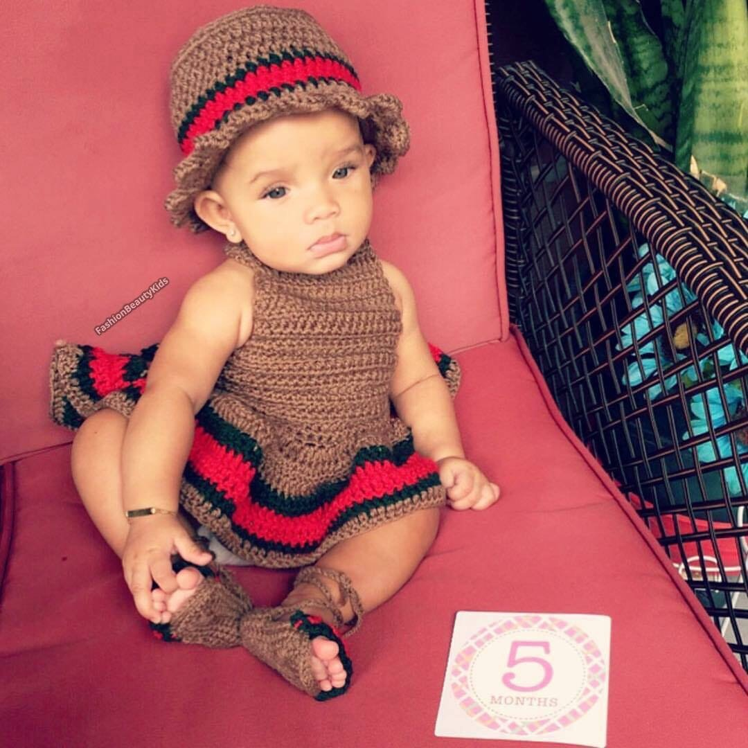 Baby girl wearing a crochet brown dress and hat with the red and green gucci stripe
