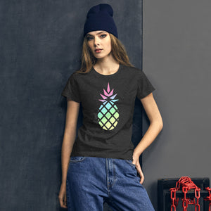 Lifestyle picture of a woman wearing a dark grey women's t-shirt with a big gradient pastel rainbow pineapple graphic.