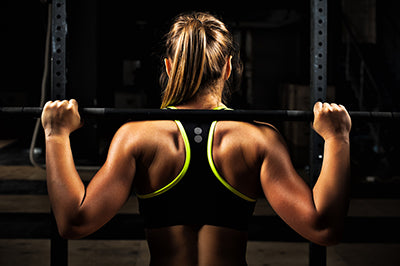 woman back lifting bar setting goals for fitness