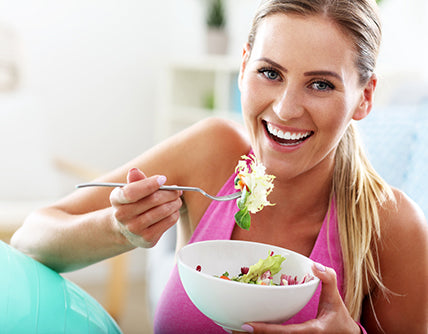 woman eating healthy salad creating your own diet and fitness routine
