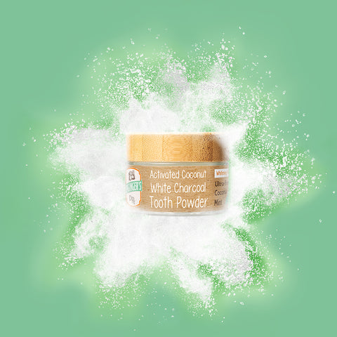 Dr. Ginger's Activated Coconut White Charcoal Tooth Powder Product shown in rendering with splash of white powder surrounding product