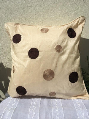 Cream cushion cover with brown embroidered circles.