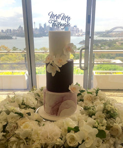 3 tiered wedding cake with marble base sugar flowers and wooden cake topper