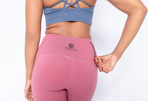 Shakolo high neckline bra in dark blue and high waist leggings in pink back view model with a hand on the zipper