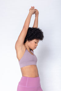 Shakolo adjustable strap bra in purple and high waist leggings in purple front view with arms in the air close up