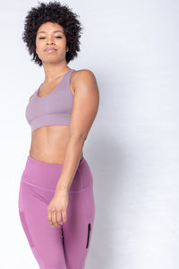 Shakolo adjustable strap bra in purple and high waist leggings in purple front view with model arm in front