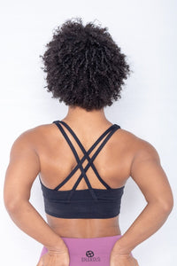 Shakolo crossover bra in black and high waist leggings in purple back view model with arms on top of butt