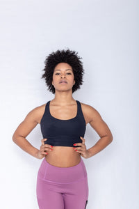 Shakolo crossover bra in black and high waist leggings in purple front view model with arms on waist